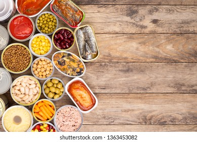 Canned food on wooden background, top view with copy space