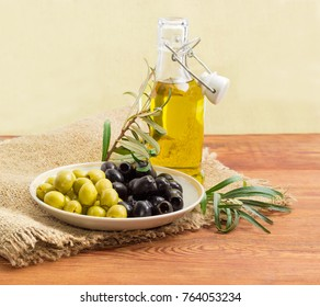 Canned green and black table olives on the saucer, olive branches and bottle of the olive oil with open lid on a sackcloth, on a wooden surface