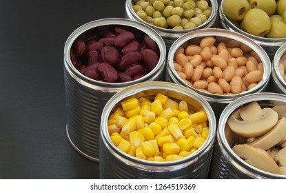 Canned green peas, beans, corn, olives and mushrooms in tin cans. Preserved food on black table.