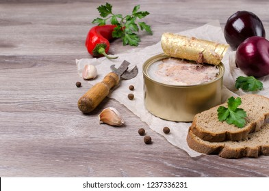 Canned meat fillet in a metal can on a wooden background. Selective focus.