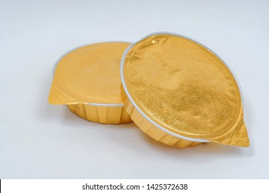 Canned pate on a white background. Canned food in gold packaging. Foil packaging for pate