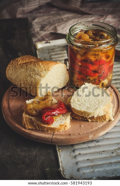Canned peppers with bread on the kitchen board (antipasti) on the table