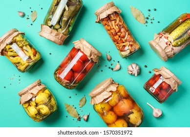 Canned and preserved vegetables in glass jars over blue background. Top view. Flat lay. Copy space