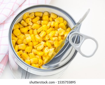 Canned sweet corn in a tin can with pull tab on a table. Side dish and ingredient for salads. Vegetarian food. Top view.