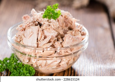 Canned tuna with fresh parsley (detailed close-up shot) on wooden background