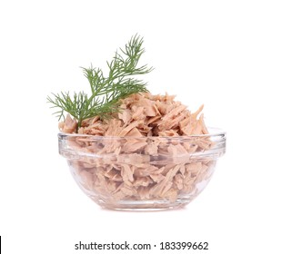 Canned tuna in glass bowl and dill. Isolated on a white background.