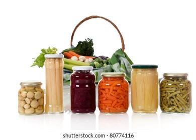 Canned vegetables in jars versus fresh vegetables in basket. Focus on jars. Healthy eating concept. Studio shot. White background. Copy space.