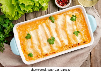 Cannelloni with filling of ground beef, tomatoes, baked with bechamel tomato sauce, top view, old dark wooden background
