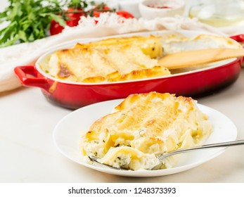 Cannelloni with filling of ricotta and parsley, baked with béchamel sauce, side view, white marble background