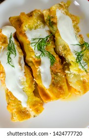 Cannelloni with meat filling in a cream sauce on a plate