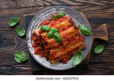 Cannelloni with mincemeat in tomato sauce, rustic wooden surface, top view