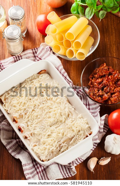 Cannelloni stuffed with meat cooked in a casserole dish ready for baking. Italian cuisine. Top view
