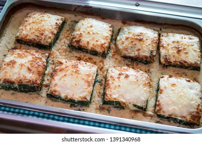 cannelloni. Cannelloni stuffed with spinach with different melted cheeses in an aluminum tray for self-service or take-away meals served in rations.