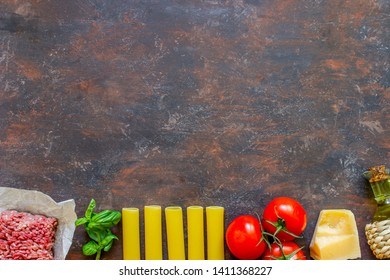Cannelloni, tomatoes, minced meat and other ingredients. Dark background. Italian cuisine.