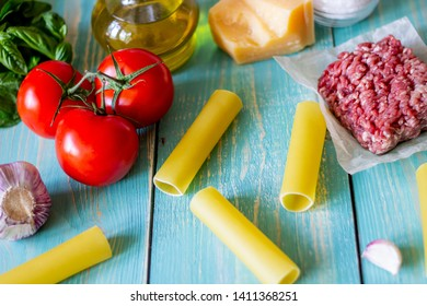 Cannelloni, tomatoes, minced meat and other ingredients. Blue wooden background. Italian cuisine.