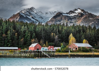 Cannery located in bay of Pacific Ocean is a part of famous fishing village Haines in Alaska in background with mountains and glaciers covered with snow during warm autumn sunny day