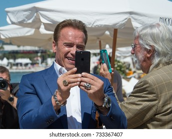 """CANNES, FR - May 20, 2017: Arnold Schwarzenegger & Jean-Michel Cousteau at the photocall for """"Wonders of the Sea 3D"""" on the beach at the 70th Festival de Cannes"""