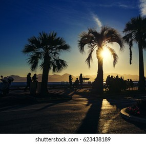 CANNES, FRANCE -  20 February, 2016: Dramatic winter sunset with blue golden tones and intense sun flare on the Croisette in Cannes