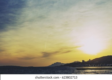 CANNES, FRANCE - 30 January, 2016: Mediterranean sea view from Golfe Juan at dusk with sun flare, with the Lerins Islands, the harbour and Cannes's coastline in the distance