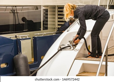 CANNES, FRANCE - APRIL 2019: Crew member on the back of a superyacht securing a mooring line after berthing in Cannes harbour