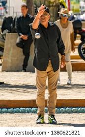CANNES, FRANCE - APRIL 2019: Man throwing a boule in a game of boules on a sandy pitch area in Cannes town centre