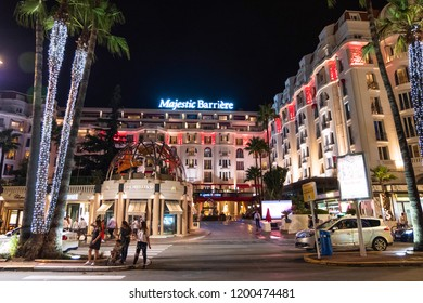 CANNES, FRANCE - AUGUST 9, 2018: Majestic Barriere hotel at night. People on the roads and street lights