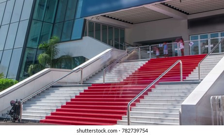 CANNES, FRANCE - CIRCA AUGUST 2017: Red carpet stairway at Palais des Festivals et des Congres timelapse in Cannes, France. Sunny summer day. Tourists making a pictures