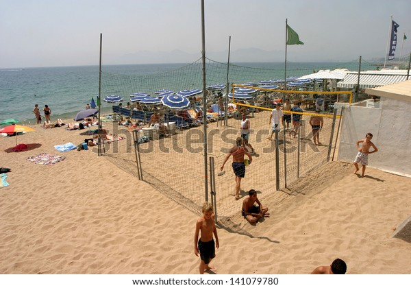 CANNES, FRANCE - JULY 24: People sunbathing and playing volleyball at Cannes Beach on July 24, 2006 in Cannes, France. Cannes beachfront, considered between 5 best urban beach of the Europe.