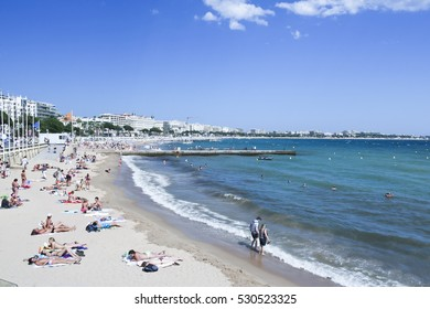 CANNES, FRANCE - JUNE 2, 2015: People on the most popular public beach in Cannes, France - Plage de la Croisette - Cannes beachfront, considered between 5 best urban beaches of Europe.