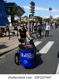 Cannes, France - May 11, 2018:  An unidentified woman cycles a bike filled with Hollywood Reporter magazines to distribute to the crowd at the 71st Cannes Film Festival.