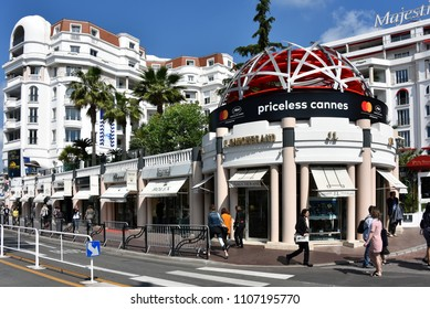 Cannes, France - May 11, 2018: Boulevard de la Croisette which contains high-end shops such as Rolex, C Gaucherand and an ad for the Film Festival.