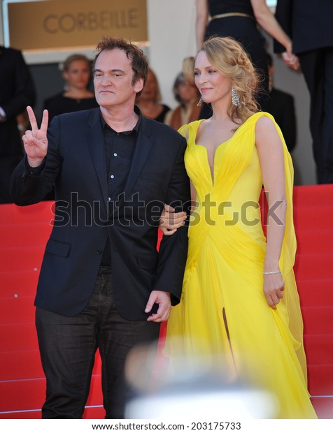 """CANNES, FRANCE - MAY 23, 2014: Uma Thurman & Quentin Tarantino at 20th anniversary screening of their movie """"Pulp Fiction"""" at the 67th Festival de Cannes."""