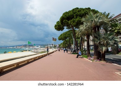 """CANNES, FRANCE - MAY 6: Pedestrians walking on the famous """"La Croisette"""" Boulevard on May 6, 2013 in Cannes, France. It is a symbol of the Cote d'Azur."""