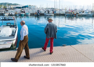 CANNES, FRANCE - OCTOBER 23, 2017: Two unknown elderly men walking along the harbor of Cannes