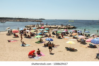 CANNES, FRANCE-AUG. 21, 2017:  A popular tourist destination on the Mediterranean coast, the beach at Cannes attracts numerous sunbathers.