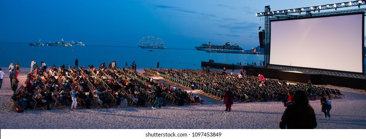 "CANNES,FRANCE-MAY.24: people takes place in the temporry ""cinema on the plage"" , cinema on the beach, at night on the  croisette of cannes during the film festival on the 24th of may 2018 in cannes,Fr"