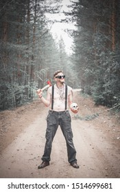 Cannibal Man in glasses with ax and skull outdoor