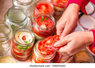 Canning fresh tomatoes with onions in jelly marinade. A shot of woman hands putting tomato slices in jars and basil leaves on top of red ripe tomato slices and onions. Vegetable salads for winter.
