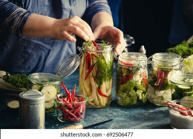 Canning green beans with red hot chili peppers in glass jars with pickled cabbage cauliflower broccoli sour preserved hands add herbs fermented process