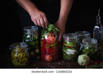 Canning jars filled with cucumbers tomato, green beans chili peppers and seasonings in preparation for making pickles hands canning food