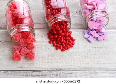 Canning jars laying on their sides filled with candy hearts and for Valentine's Day  on a rustic wood table.