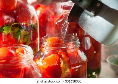 Canning process of tomato in mason jar. On background is few jars with tomatoes. Conservation and cooking