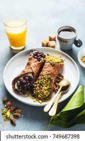 Cannoli with ricotta, chocolate and pistachios. Italian pastries of the Sicily . classic breakfast with orange juice and coffee