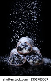 Cannolis being decorated with powdered sugar on a solid black background