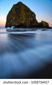 Cannon Beach during the early glow of sunrise as a wave runs into the foreground with power.