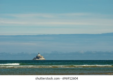 Cannon Beach Oregon USA - July 21, 2017, Ocean and blue sky with mountains on horizon