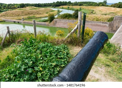 Cannon, green water and dam in Veere. The Netherlands