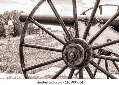 Cannon on a Louisiana Levee by the Mississippi River. In the distance one can see another cannon between the spokes of the iron wheel. This is a sepia image.