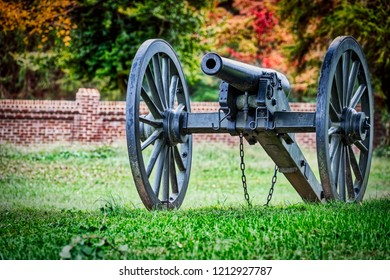 A cannon sitting from the American Civil War sits on a Virginia field. with a fall forest in the backgound.