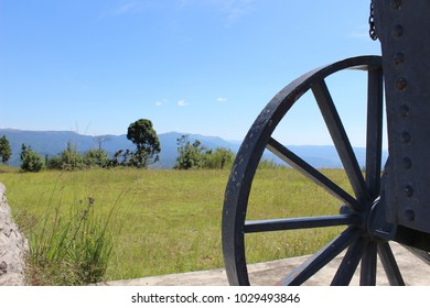 Cannon wheel silhouetted against lush green grass and blue sky